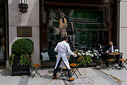 Alongside customers enjoying drinks, a waiter sweeps and tidies the pavement outside the Ralph Lauren on New Bond Street, on 12th July 2021, in London, England.