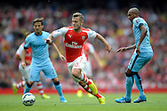 Arsenal's Jack Wilshere breaks away from Manchester City's Fernandinho. Barclays Premier league match, Arsenal v Manchester city at the Emirates Stadium in London on Saturday 13th Sept 2014.<br /> pic by John Patrick Fletcher, Andrew Orchard sports photography.
