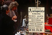 "Bargain-hunters look through antiques in the flea market at the Marché du Jeu de Balle, in the Marolles district, Brussels. Two momen admire a small glass that one holds in her hand, in front of a sign written in Belgian French telling visitors that furniture, coins, books, dolls, games can be bought and sold here. At Place du Jeu de Balle Flea Market, you can find an extraordinary mix of household items, vintage clothes, crockery and furniture. This market is open daily from 6am to 2pm and is in the heart of the ""Marolles"" district, a working-class neighbourhood built in the 17th century."