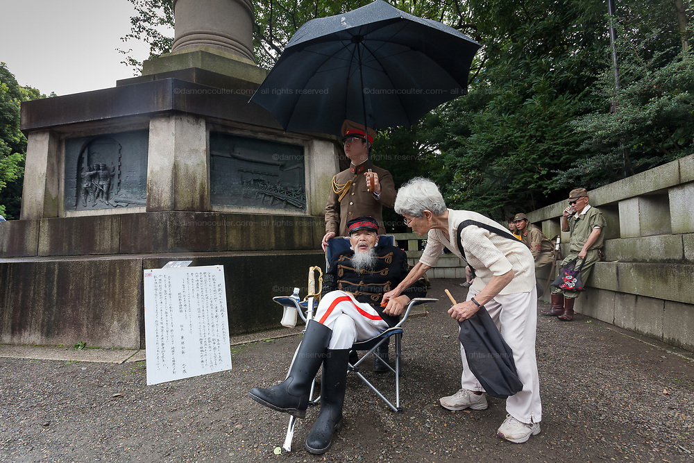 Right-winger, Hakugaku Kuribayashi (seated) talks with his wife as Yasukuni shrine marks the 72nd anniversary of the end of the Pacific War. Yasukuni Shrine, Kudanshita, Tokyo Japan. Tuesday August 15th 2017. Nominally a event to honour Japan's war dead and call for continued peace, this annual gathering  at Tokyo's controversial Yasukuni  Shine also allows many Japanese nationalists to display their nostalgia for their Imperial past.Rightwing paramilitary groups, Imperial cos-players, politicians and many ordinary citizens come together at the shrine to march and wave flags. The day goes almost unreported in the mainstream Japanese media.