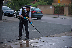 ©Licensed to London News Pictures 06/09/2020  Lewisham, UK. A policeman jet washing blood of the pavement. A murder investigation has been launched in Lewisham, South East London following the stabbing of a 34 year old man who was found with a wound to his neck in the early hours of Sunday morning. The man was pronounced dead at the scene.<br />  Photo credit: Grant Falvey/LNP
