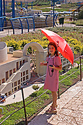 A young girl with a red umbrella near a replica at mini Israel, Mini Israel is a park of scaled down models of sites and building in Israel, All models are exact copies of  the sites, buildings and landscapes from around the country built at a scale of 1:25