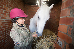 Musician Kate Miller with her horse Nad-e-ali. Band of the Household Cavalry at their stables in Tower Farm, Liberton, Edinburgh