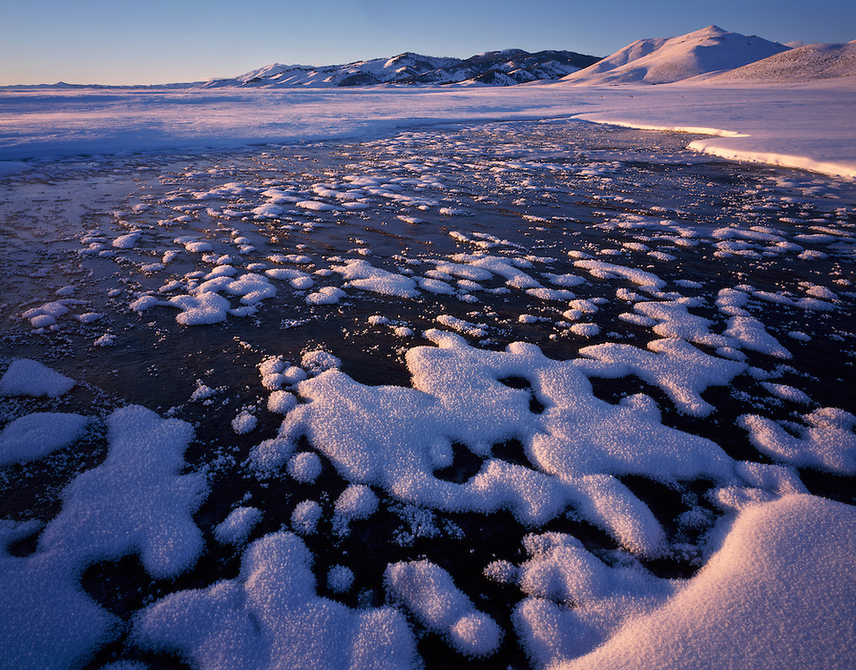 Frozen spring on the Camas Prairie in Southwest Idaho has clumps of ice crystals creating a mosaic pattern in waters surface in the alpenglows last light of the day.