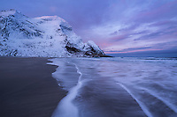 Winter sunrise over snow covered mountain peaks rising above Bunes beach, Moskenesøy, Lofoten Islands, Norway