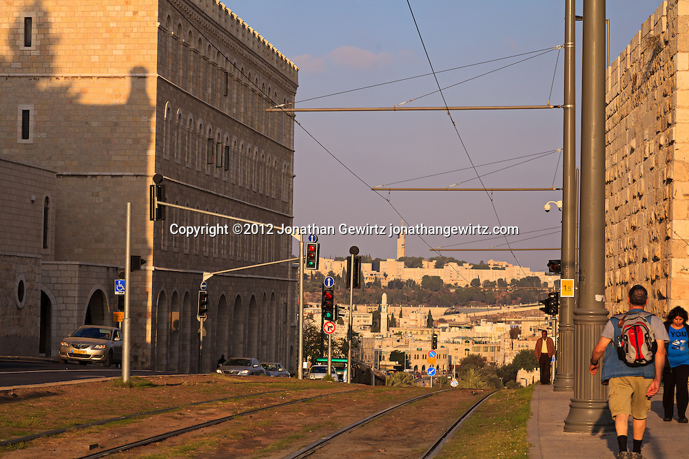 Tracks for Jerusalem's light rail system pass between Sultan Suleiman Street and the walls of the Old City of Jerusalem. Mount Scopus is visible in the distant background. WATERMARKS WILL NOT APPEAR ON PRINTS OR LICENSED IMAGES.