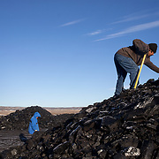 Darryl Sahmea (right) and Dertram Ami (Polacca, AZ) search for quality pieces of coal, February 4, 2017, at the public loadout facility in the Kayenta Mine, Arizona.
