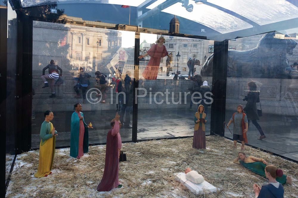 A holy nativity scene titled Christmas Crib by the artist Tomoaki Suzuki with background tourists in London's Trafalgar Square. As three girls all climb together the plinth that is below Nelson's comumn, encased within a transparent perspex box are the pilgrims who are apparently paying their respects to the infant Jesus in that famous Christian religious event. The new crib was commissioned in 2006 by St Martin-in-the-Fields providing a significant new public art work embodies characters representing different ethnicities - Middle eastern, Caucasian, African and Asian. The 11 painted lime wood carving are 40% life-size and were a collaboration with fashion designer Jessica Ogden who created timeless silk costumes for each of the characters.