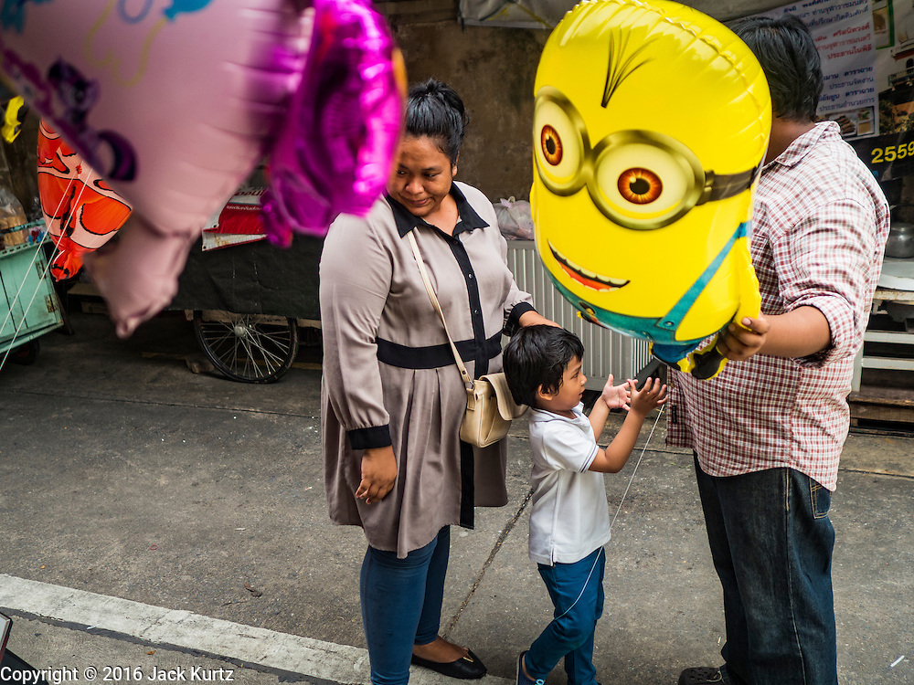 """12 SEPTEMBER 2016 - BANGKOK, THAILAND:  A family buys an inflatable """"Minion"""" toy during the celebration of Eid al-Adha at Haroon Mosque in Bangkok. Eid al-Adha is also called the Feast of Sacrifice, the Greater Eid or Baqar-Eid. It is the second of two religious holidays celebrated by Muslims worldwide each year. It honors the willingness of Abraham to sacrifice his son, as an act of submission to God's command. Goats, sheep and cows are sacrificed in a ritualistic manner after services in the mosque. The meat from the sacrificed animal is supposed to be divided into three parts. The family retains one third of the share; another third is given to relatives, friends and neighbors; and the remaining third is given to the poor and needy.         PHOTO BY JACK KURTZ"""