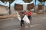 A young Syrian girl takes plastic to her tent to cover a leak during rain in Yayladagi refugee camp for Syrians in southern Turkey. 12/21/2012 Bradley Secker for the Washington Post