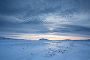 Wintry sun and cloud formation above snow-covered mountains and landscape of lava fields in South Iceland