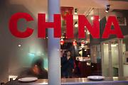 Chinese restaurant staff prepare under the word China on the window. Chinatown, London