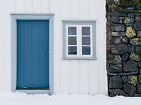 Blue door and window of Grenjaðarstaður Turf Farm in winter. North Iceland.
