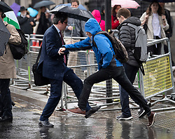 © Licensed to London News Pictures. 08/05/2019. London, UK. People leap over a puddle in Westminster in London as wet and windy weather hits the capital. Heavy rain is forecast for most of the UK this week. Photo credit: Ben Cawthra/LNP