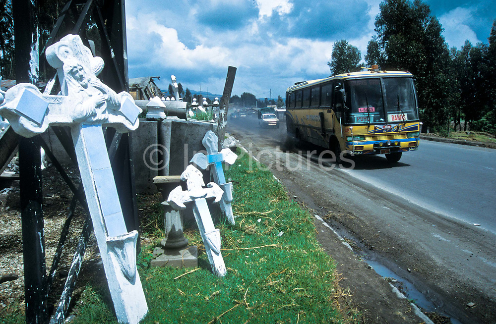 A long distance bus travels along the Panamerican Highway past a maker and seller of cemetry crucifixes, a reflection of the high number of deaths on the highway due to often recless driving.  Heading to the country's capital Quito, Ecuador