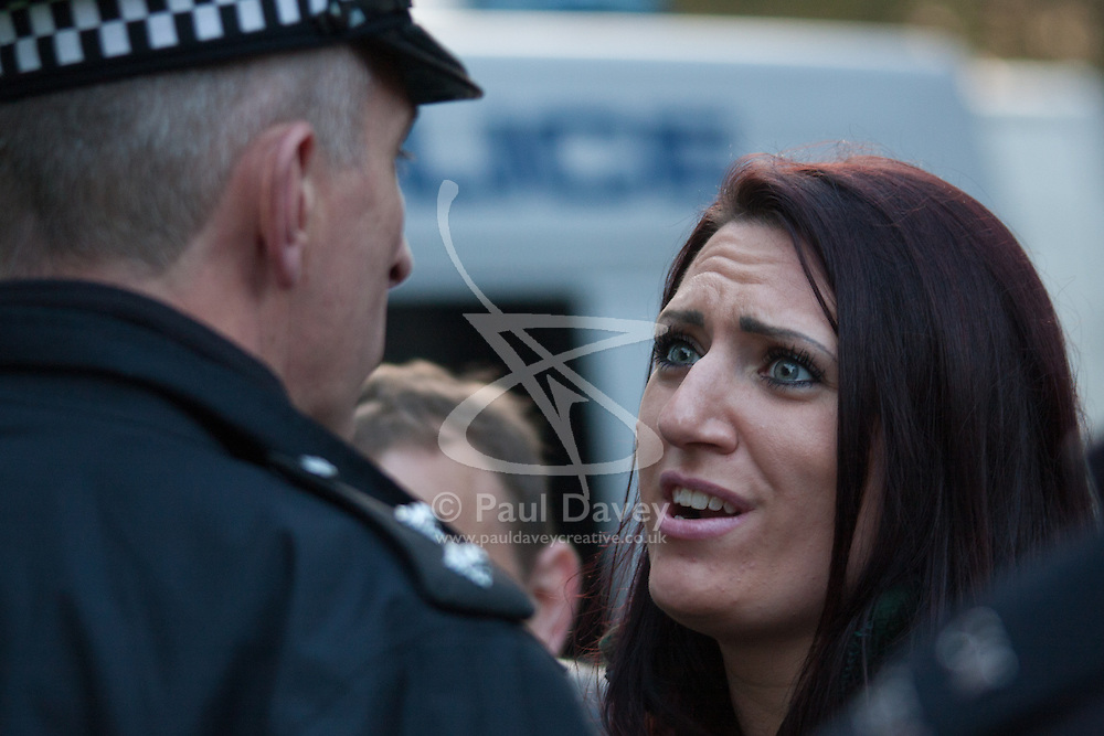 "Mayfair, London, November 28th 2014. A protest against Egypt's leader Al-Sisi descended into moinor scuffles as right wing ""patriots"" from anti-Islamic group Britain First arrived to protest against the presence of Islamist preacher Anjem Choudary, who was recently arrestred as part of an ant-terror operation. Playing patriotic British Music, Britain First accused Muslims of worshiping a ""devil"" and a ""paedophile prophet"". Police had to intervene before hotheads on both sides became violent. PICTURED: Jayda Fransen, Deputy Leader of Britain First argues with a police officer who ordered her to turn down their music."