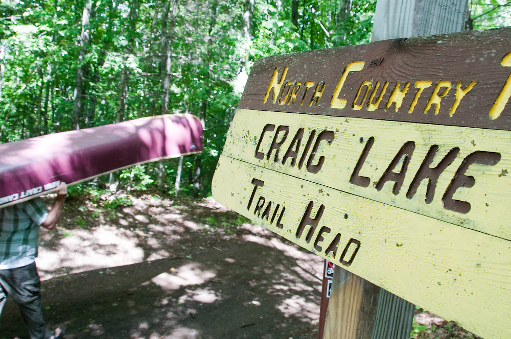 Trail signs and canoeist at Craig Lake State Park near Michigamme Michigan.