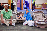 "Sept. 10 - GLENDALE, AZ: A family waits for prayers to start in the Glendale Civic Center. Muslims from the Phoenix area celebrated Eid ul-Fitr, the end of Ramadan, at the Glendale Civic Center in Glendale, AZ, a suburb of Phoenix. Eid ul-Fitr, often abbreviated to Eid, is the Muslim holiday that marks the end of Ramadan, the Islamic holy month of fasting. Eid is an Arabic word meaning ""festivity"", while Fitr means ""conclusion of the fast""; and so the holiday symbolizes the celebration of the conclusion of the month of fasting from dawn to sunset during the entire month of Ramadan. The first day of Eid, therefore, is the first day of the month Shawwal that comes after Ramadan.  Photo by Jack Kurtz"