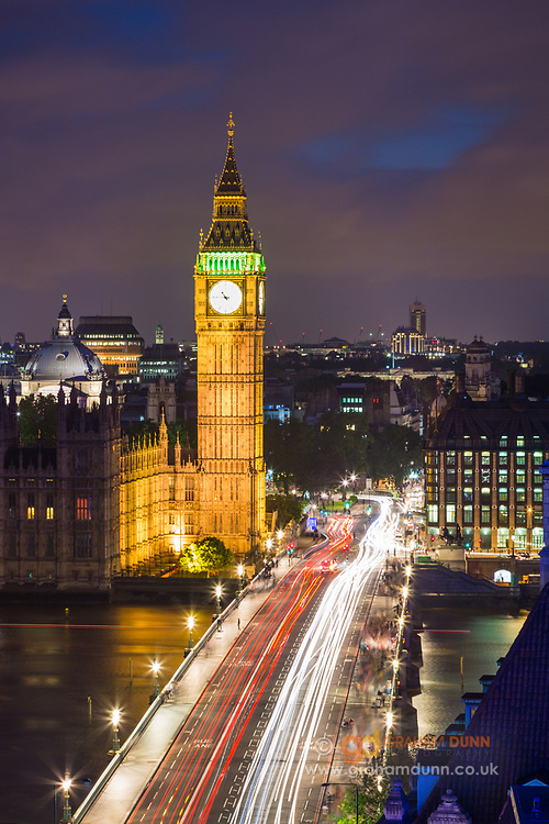 Traffic & pedestrians flow across Westminster Bridge towards Big Ben and the Palace of Westminster. An iconic night cityscape view of London. Urban landscape photography at twilight in England's capital city, UK.