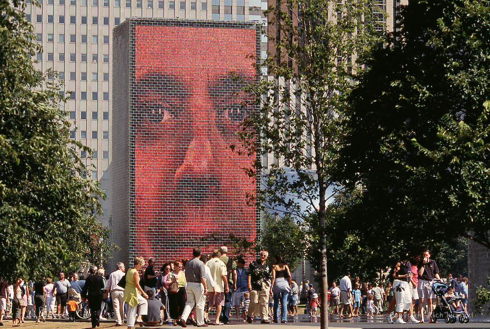 Visitors at The Crown Fountain in Millenium Park, Chicago, Illinois. The 50-foot glass block tower is one of two designed by Jaume Plensa, which projects video images of faces of Chicago citizens onto an LED screen.