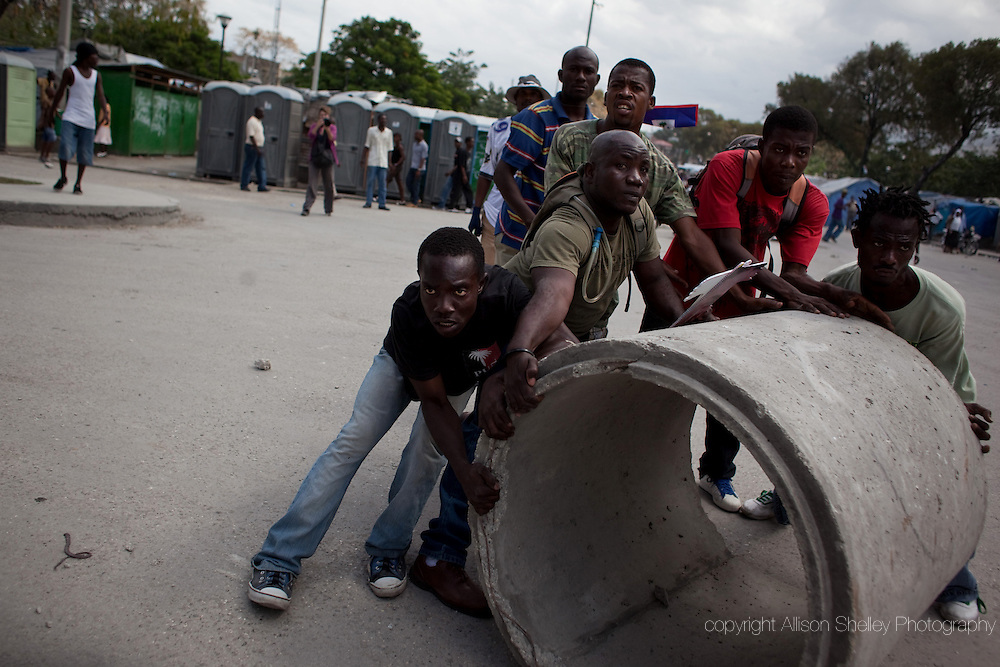 """Men prepare to roll a giant concrete pipe down the street at Haitian police as Haitians shouting """"Revolution"""" took to the streets to demand that Haitian president Rene Preval leave office in Port-au-Prince, Haiti, February 7, 2011. Though he has parliamentary approval to stay in office until May 14, Preval's official mandate as president expires today.  Haitian elections were delayed-- first by the 2010 earthquake and then by the need for a run-off between challenging candidates."""