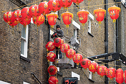 © Licensed to London News Pictures. 09/02/2021. London, UK. Members of the Chinese community put up red lantern street decorations in London's Chinatown. Because of the current Covid-19 lockdown restrictions, there will not be the annual public celebrations for Year of the Rat. Photo credit: Ray Tang/LNP
