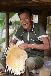 Talot, 57 years old is a member of the Older People's Group. He makes traditional baskets and sticky rice steamers from fine slithers of bamboo.  His does not travel to the upland fields as he is not strong enough, but makes and income from this local production he completes at home.<br /> Had Khen Village, Pakseng District, Luang Prabang Province, Lao PDR