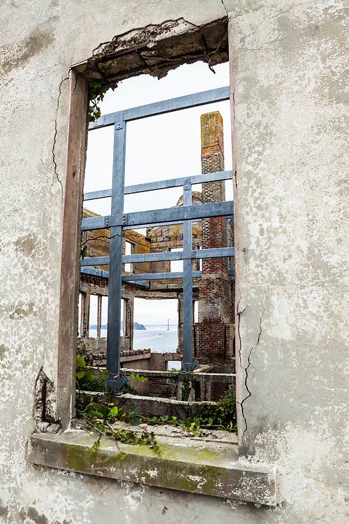 Looking through a window in an old weathered building on Alcatraz Island / Prison seeing through the building to the bay beyond and the Bay Bridge, California, USA.