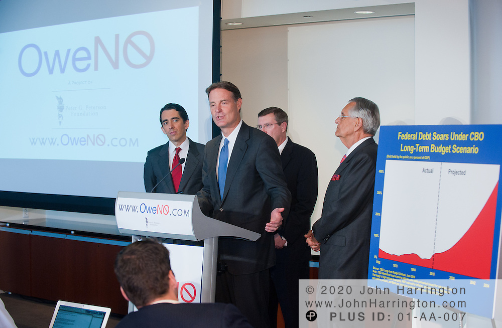 """Senator Evan Bayh (D-IN) speaks as the Chairman of the Peter G. Peterson Foundation Peter G. Peterson (far right), Vice Chairman Micheal A. Peterson, and U.S. Senate Budget Committee Chairman Kent Conrad (middle back) look on at the press conference launching the """"OweNo"""" campaign at the Newseum in Washington D.C. on November 9th, 2010. The goal of the campaign is to create an effective bipartisan movement to find solutions to the country's fiscal challenges."""