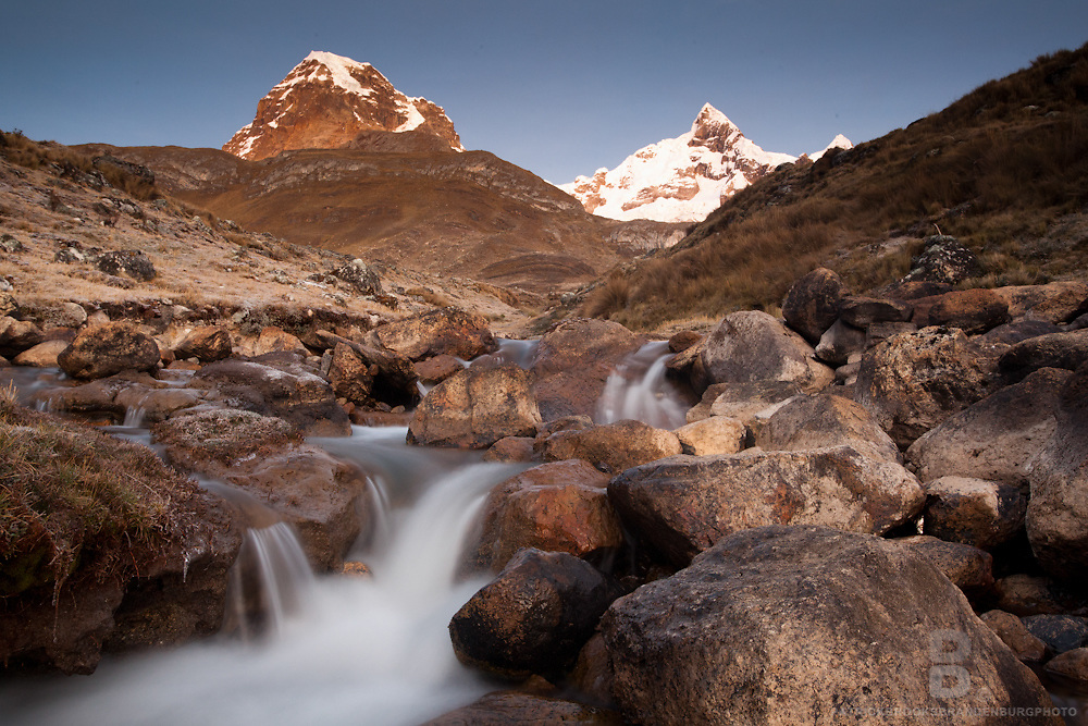 A long exposure of a creek rushing through boulders during surise over Mt Trapecio to the left and Jurau to the right located in the Cordillera Huayhuash of the Andes Mountains in Peru.