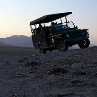 Africa, Namibia, Puros. Safari jeep in the rugged landscape of Puros Conservancy.