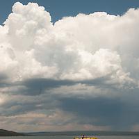 Kayakers on Yellowstone Lake, under summer thunderstorm cloud, Wyoming