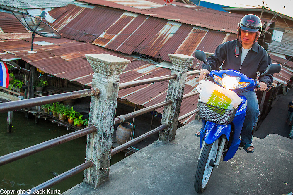 13 JANUARY 2013 - BANGKOK, THAILAND:  A man rides his motor scooter across Khlong Bang Luang in Bangkok. The Bang Luang neighborhood lines Khlong (Canal) Bang Luang in the Thonburi section of Bangkok on the west side of Chao Phraya River. It was established in the late 18th Century by King Taksin the Great after the Burmese sacked the Siamese capital of Ayutthaya. The neighborhood, like most of Thonburi, is relatively undeveloped and still criss crossed by the canals which once made Bangkok famous. It's now a popular day trip from central Bangkok and offers a glimpse into what the city used to be like.     PHOTO BY JACK KURTZ