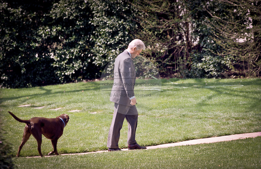 US President Bill Clinton walks with his dog Buddy to the Oval Office after returning from Camp David March 29, 1999 at the White House in Washington D.C.