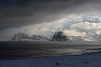 Dramatic light of winter storm clouds sweeping over distant mountains of Vestvågøy, Lofoten Islands, Norway