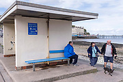 A man in blue sits on a blue bench as a coupe walk past with their pet dog on the seafront promenade at Llandudno, on 4th October 2021, in Llandudno, Gwynedd, Wales.