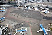 Nederland, Noord-Holland, Haarlemmermeer, 16-04-2008; geparkeerde vliegtuigen op luchthaven Schiphol; linksboven het stationsgebouw (terminal) en vliegtuigen aan de gates (de 'slurven'); het KLM vliegtuig (rechtsonder) is achteruit geduwd (de push-back) en staat klaar om om eigen kracht (voorwaarts) naar de startbaan te taxien;.bagage wordt aan boord gebracht, vliegtuigen worden beladen, ..luchtfoto (toeslag); aerial photo (additional fee required); .foto Siebe Swart / photo Siebe Swart