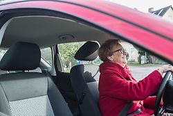 Happy old woman driving a car
