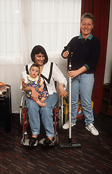 Woman with disability; who is wheelchair user; holding baby on knee while carer prepares to hoover floor,
