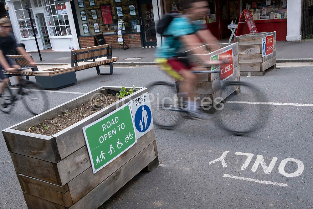 A blurred cyclist passes through the barriers that form an LTN Low Traffic Neighbourhood, an experimental closure by Southwark Council preventing motorists from accessing the junction of Carlton Avenue and Dulwich Village. Restrictions also prevent traffic from passing through at morning and afternoon rush-hour times in the borough of Southwark, on 14th June 2021, in London, England.