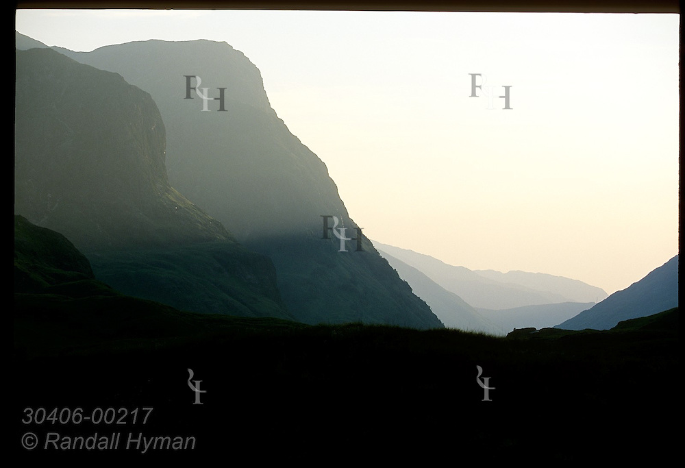 Silhouetted mountains recede in the hazy light of a July eve in view from saddle in upper Glen Coe; Glencoe, Scotland.