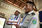 Out-reach peer-peer education to school children. Here police officer June Bunreon goes through the LAC produced flip chart of petty crimes and social issues and talk them over with the children.Legal Aid Cambodia  tries through out-reach education in schools to prevent children from falling into crime and teach them their rights.LAC also offer legal aid to children arrested and sent to prison, many of them without any legal representation.