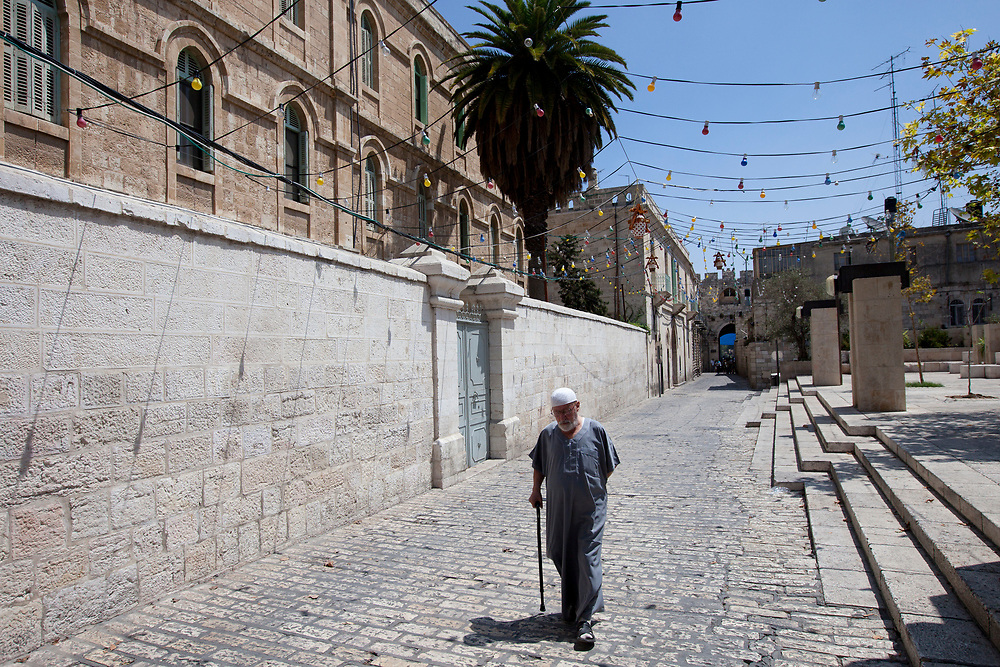 A Palestinian man walks down an alley, as Muslims make their way through Jerusalem's Old City to attend prayers at the Al Aqsa Mosque on the first Friday of the Muslim holy month of Ramadan, on August 13, 2010.