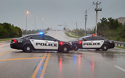 Police block a road leading to the ocean front as Hurricane Irma makes landfall in Hollywood, Fla., Saturday, September 9, 2017. THE CANADIAN PRESS/Paul Chiasson
