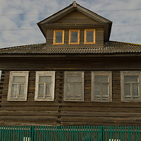 An aging, traditional Russian log house stands by a road leading into the northern port of Arkhangel'sk.