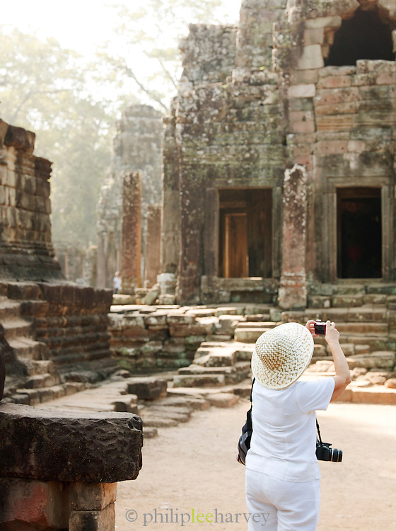 A tourist taking a picture in the Bayon temple at Angkor, Siem Reap Province, Cambodia