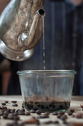 Man pouring hot water in a glass with coffee powder