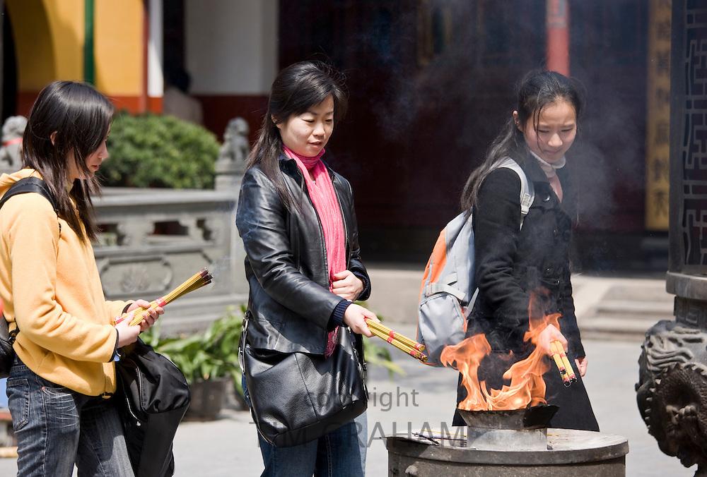 Worshippers burn incense at the Jade Buddha Temple, Shanghai, China