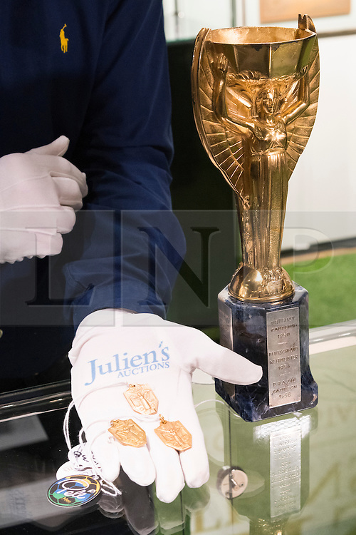 © Licensed to London News Pictures. 01/06/2016. Jules Rimet Trophy (Est £280,000-£420,000) and a selection of medals including 1970 FIFA World Cup Winner's Medal, 1962 FIFA World Cup Winner's Medal, 1958 FIFA World Cup Winner's Medal. Est £70,000-140,000 each. Items from the Pele: The Collection with over 1,500 items of memorabilia owned by Pele for sale on later in June. London, UK. Photo credit: Ray Tang/LNP