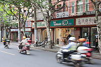 local street scene in shanghai with motorbikes and shops